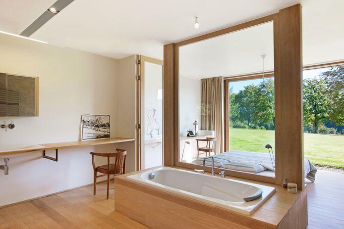 La baignoire en solo est séparée du lit par un grand cadre en bois garni d'une vitre. Pour un bain relaxant au milieu de la nature.