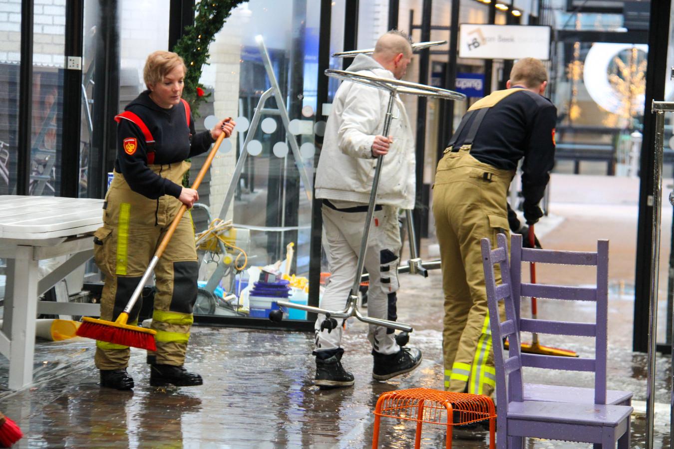 Brandweerlieden zijn druk met het verwijderen van het bluswater dat in de Korenpassage uit de sprinklerinstallatie spoot.