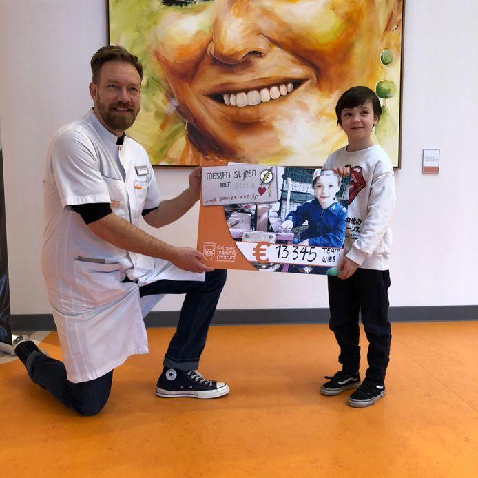 Sten Janssen uit Eindhoven overhandigt zijn cheque van 13.345 euro aan kinderoncoloog Dannis van Vuurden.