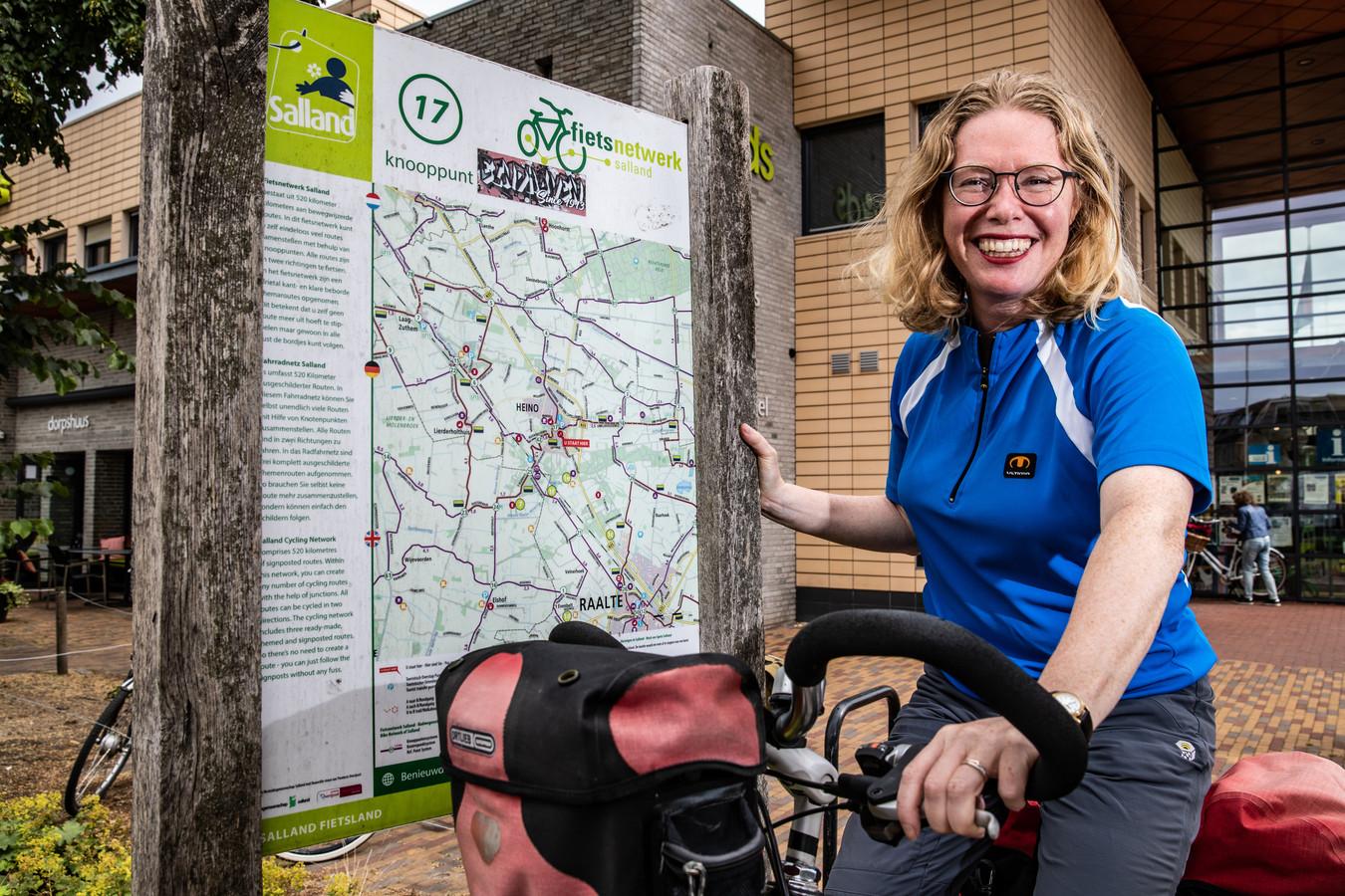 Monique van Klaveren bij het bord met fietsroutes in de buurt van het Dorpshuus in Heino. ,,Dat was maar aan één kant bestickerd, juist de kant die de meeste fietsers niet zagen als ze kwamen aangereden.''