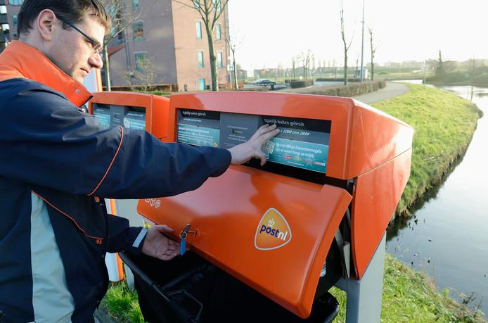 Een medewerker van PostNL leegt een brievenbus. PostNL brengt het aantal terug van 19.000 naar circa 11.000