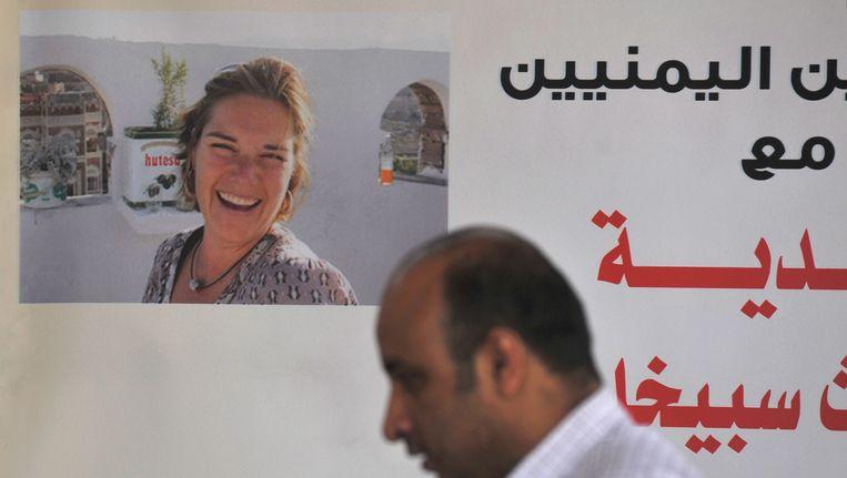 Een Jemenitische journalist in juni bij een poster van Judith Spiegel, tijdens een demonstratie tegen hun verdwijning. Beeld EPA
