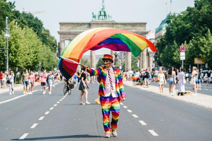 """Un participant habillé aux couleurs de l'arc-en-ciel agite un drapeau coloré devant la Porte de Brandebourg pendant le défilé du Christopher Street Day """"CSD Berlin 2021"""" à Berlin, en Allemagne, le 24 juillet 2021."""