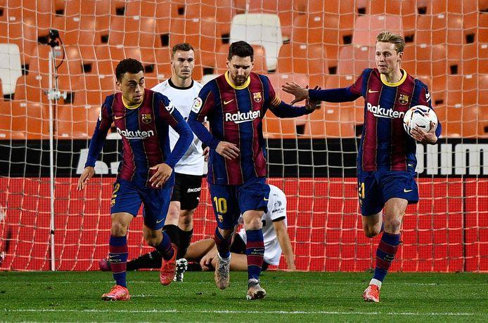 Lionel Messi viert zijn eerst goal tegen Valencia met Sergiño Dest (l) en Frenkie de Jong.