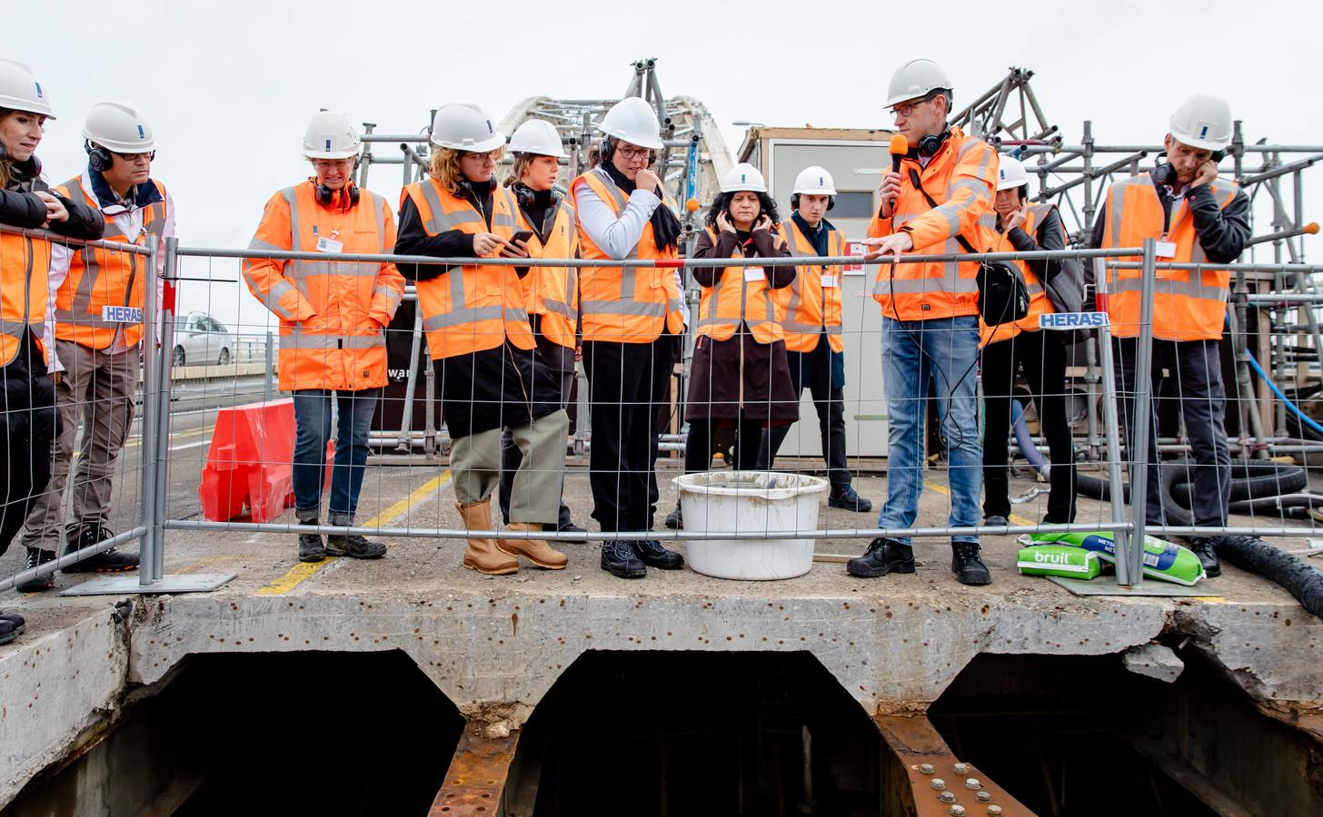 VVD-staatssecretaris Tamara van Ark (midden, met zwarte sjaal) krijgt tekst en uitleg over de chroom-6-werkzaamheden aan de Waalbrug van Marijn Rutten (man met microfoon)