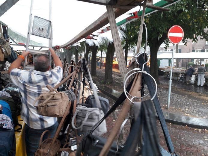 Paolo Podda houdt op weekmarkt Oisterwijk zijn kraam met lederwaren droog.