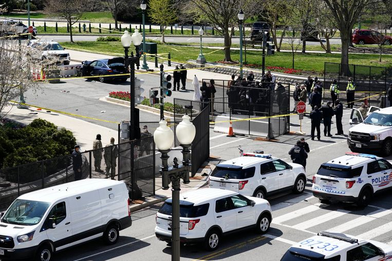 Politieagenten verzamelen zich bij een auto die tegen een slagboom op Capitol Hill in Washington is gereden Beeld AP