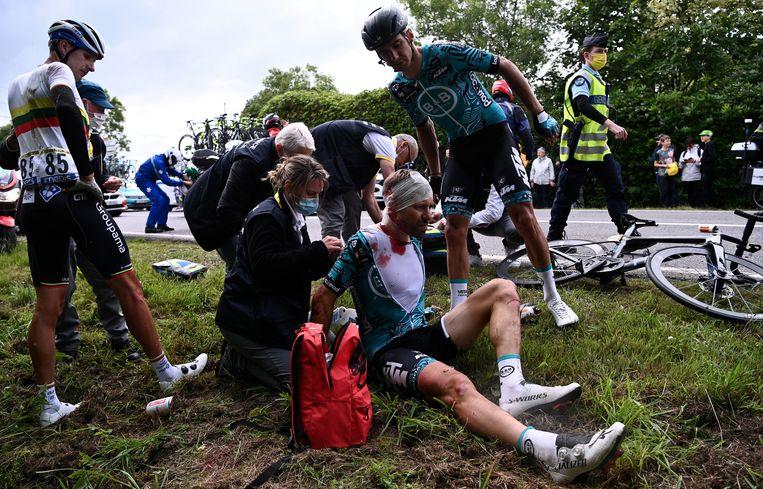 Een renner wordt verzorgd na een valpartij.  Beeld EPA