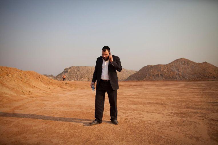 Dan Gertler telefoneert terwijl hij op een mijngebied in Congo staat. Beeld Bloomberg via Getty Images