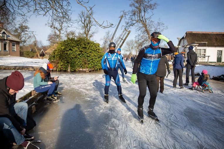 Mensen schaatsen door het dorpje Dwarsgracht, vlak bij Giethoorn. Beeld Herman Engbers