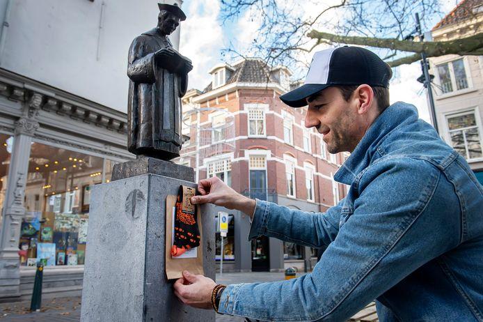 Niels Hermus hangt als lancering voor zijn sokkenproject een paar sokken op in de Veemarktstraat.