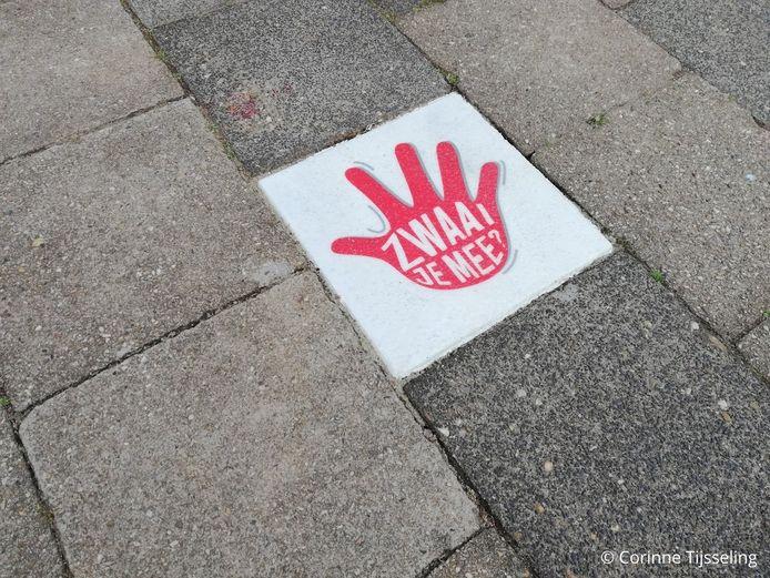De felgekleurde tegels moeten voorbijgangers aanmoedigen om even spontaan te zwaaien naar bewoners.