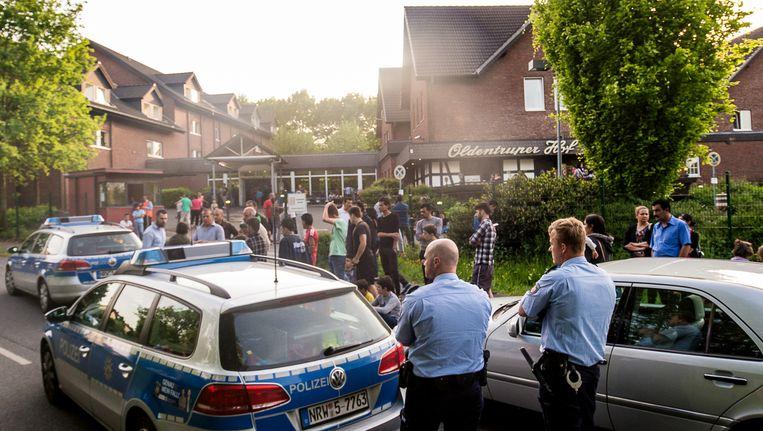 Politie en vluchtelingen staan buiten de opvang in Bielefeld. Beeld ap