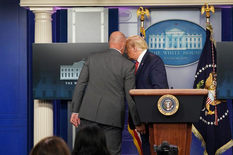 Trump wordt door een medewerker van de Secret Service onderbroken en weggeleid. Beeld REUTERS