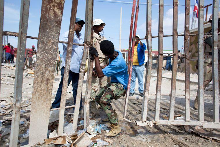Dominicaanse autoriteiten duwen een man terug over de grens naar de Haïtiaanse kant van het eiland in het grensdorp Jimani, waarvan het Haitiaanse deel Malpasse heet. Archieffoto. Beeld AP
