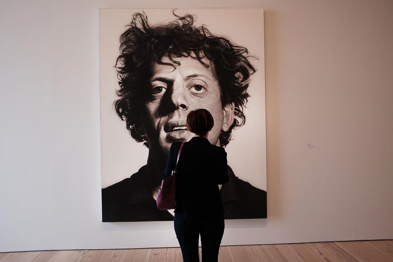 Een bezoeker kijkt naar een portret van Philip Glass, geschilderd door Chuck Close. Te zien in het Whitney Museum of American Art in New York. Beeld Getty Images