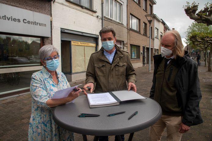 Gemeenteraadsvoorzitter Marianne Gorré en Joris Van Duffel van Urbanlink ondertekenen de samenwerking. Schepen Piet Van Heddeghem kijkt tevreden toe.