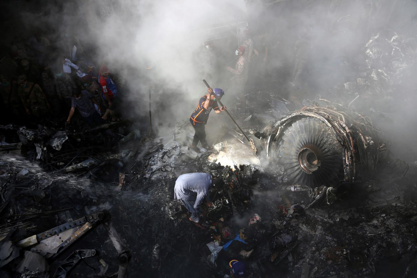 Reddingsdiensten en vrijwilligers zoeken tussen de wrakstukken van het vliegtuig naar slachtoffers.