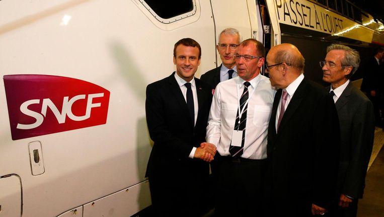 De Franse president Emanuel Macron schudt de hand van een treinmachinist die werkt op een nieuwe spoorlijn die in juli vorig jaar in gebruik werd genomen. Beeld afp