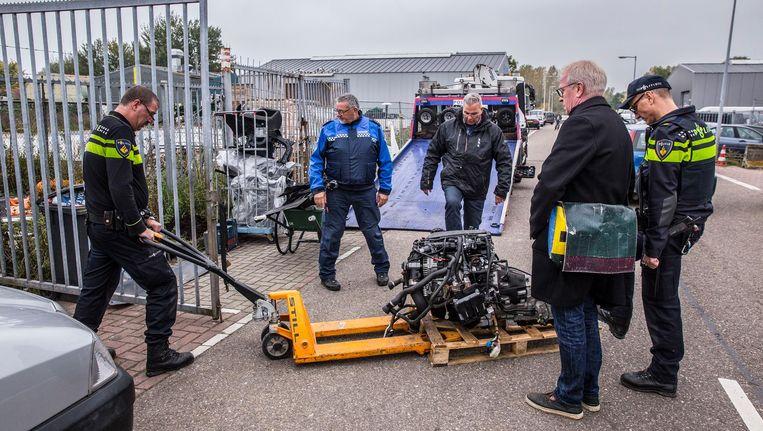De politie neemt het gestolen BMW-motorblok mee. De rest van de auto werd ook gevonden in de loods, uiteengeschroefd in tientallen stukken Beeld Amaury Miller