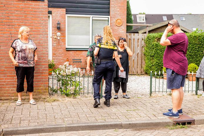 Politieagenten overleggen met de geschrokken bewoners.