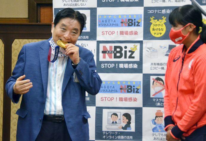 De burgemeester bijt in de gouden medaille van Miu Goto.