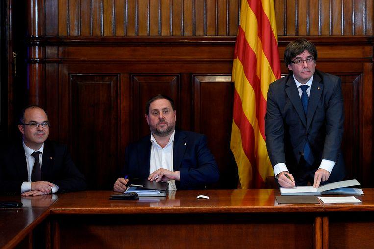 Catalaans minister-president Carles Puigdemont (rechts) tekent een onafhankelijkheidsverklaring aan de zijde van zijn viceminister-president Oriol Junqueras (midden). Junqueras werd veroordeeld tot dertien jaar cel, Puidgemont is nog steeds in ballingschap. Beeld AFP