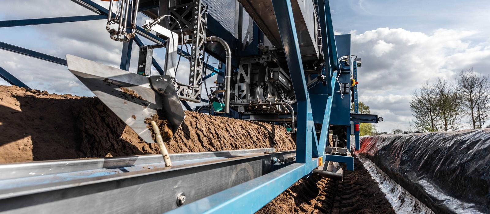De machine aan het werk op een aspergeveld.