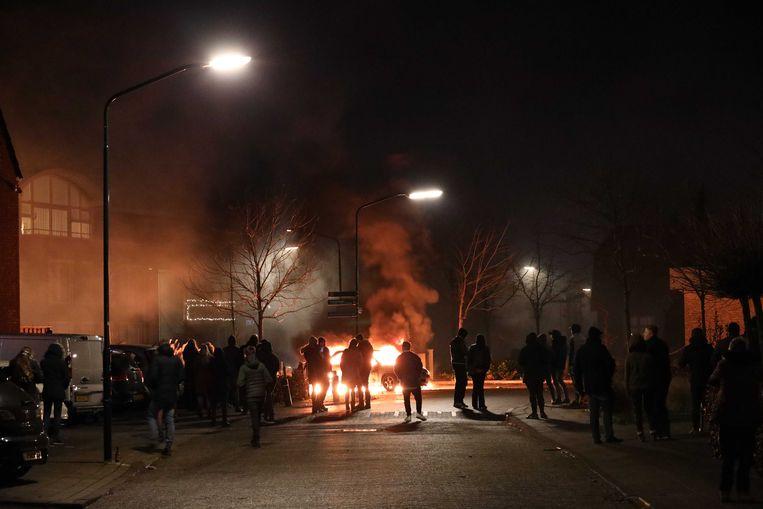 In de Brabantse plaats Veen was het voor de derde avond op rij onrustig. Inwoners staken auto's en een paardentrailer in de brand. Beeld ANP