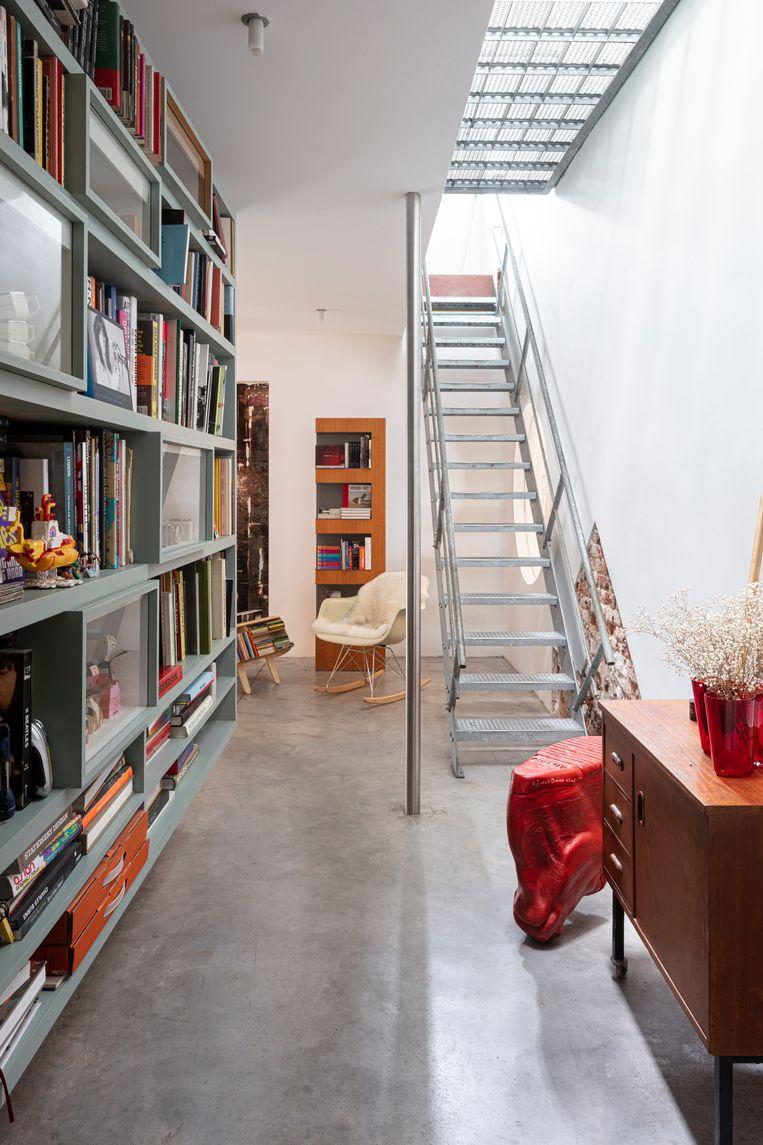 De gang tussen inkom en woongedeelte met de zelfontworpen hangbibliotheek. Op de   ahtergrond een vintage Eames-schommelstoel en daarnaast de Penguin Donkey, een boekenmeubel ontworpen door Egon Riss in de jaren dertig.  Beeld Tim van de Velde