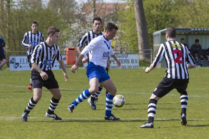 Een duel om de bal tussen Robin Versluijs (links) van Oosterhout en Barry Perk (midden) van Cluzona. f
