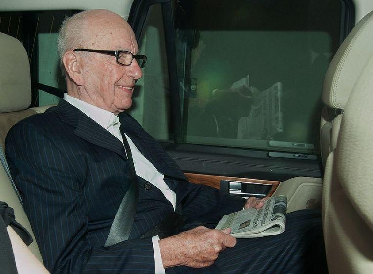Rupert Murdoch leest ook vandaag één van zijn kranten, terwijl hij in de auto zit. Beeld afp