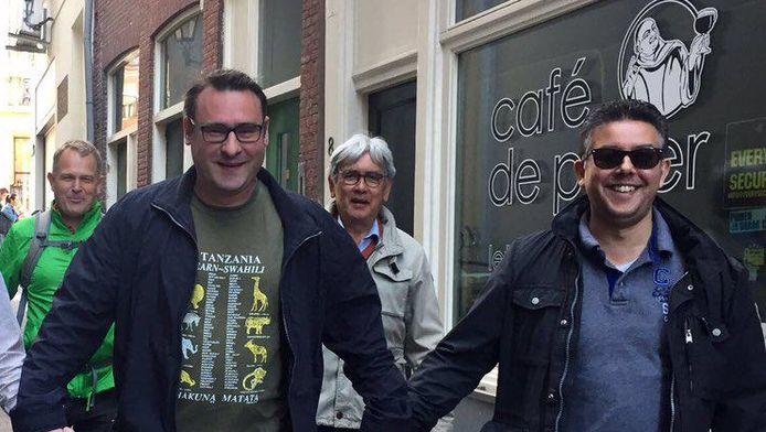 Richard de Mos hand in hand met Rachid Guernaoui - rechts - zaterdag tijdens tocht tegen homogeweld door Den Haag.