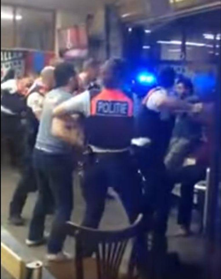 Dit beeld uit een filmpje van de vechtpartij toont hoe de agenten vuistslagen uitdeelden aan de cafégangers om ze te overmeesteren.