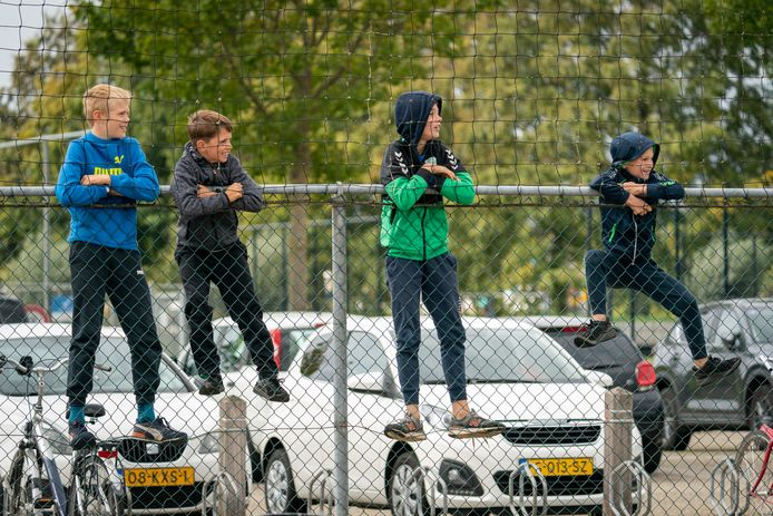 Jeugdige supporters achter de hekken om een wedstrijd te bekijken van Spero in Elst.