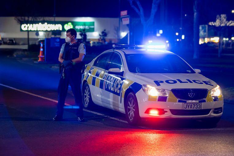 Politietroepen houden de wacht bij de supermarkt in Auckland, waar zes mensen werden neergestoken. Beeld AP
