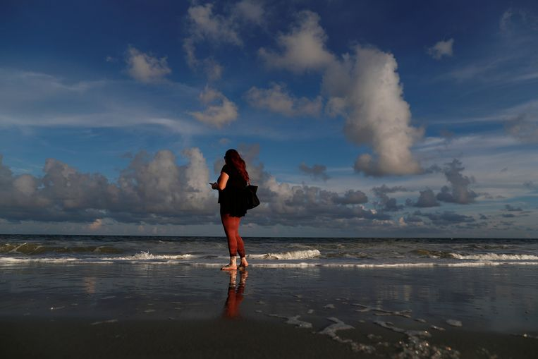 Caitie Sweeney uit Myrtle Beach sms't haar familie vanop het strand. Beeld REUTERS