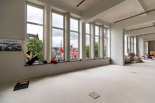 De opengebroken zaal voor de jeugdafdeling van de nieuwe bibliotheek: witte muren en hoge plafonds, veel licht en ruimte door de nieuwe ramen.