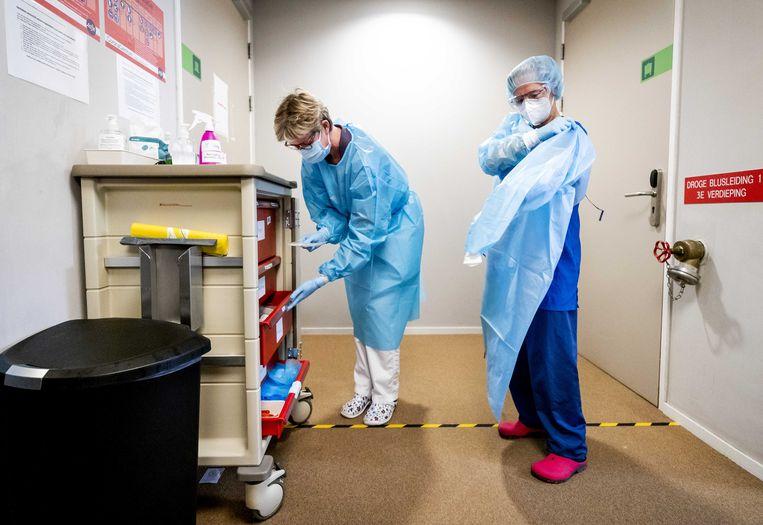 Beschermende kleding in de zorg kan een extra last zijn voor vrouwelijke werknemers die last hebben van overgangsklachten als opvliegers. Beeld ANP