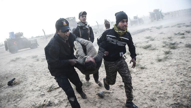 Iraakse elitetroepen dragen een strijders weg die gewond is geraakt bij gevechten tegen IS in Bazwaya, ten oosten van Mosul. Beeld afp