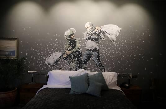 Een muurschildering van Banksy in het Walled Off-hotel, waarop een Israëlische soldaat en een gemaskerde Palestijnse man een kussengevecht houden.