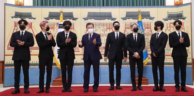 De Zuid-Koreaanse president Moon Jae-in (wit mondmasker) met de leden van popgroep BTS, voor hun vertrek naar de VN-vergadering in New York.  Beeld EPA