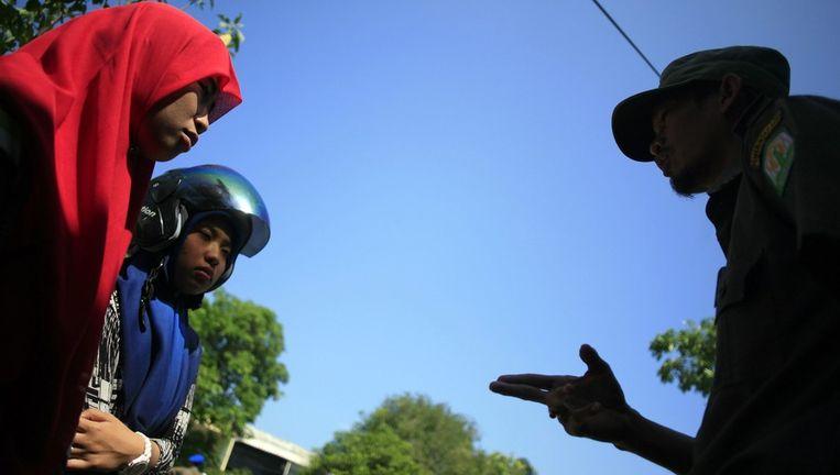 Een politieagent wijst meisjes terecht die zijn gearresteerd voor het dragen van te strakke kleding. Een archieffoto uit Indonesië. Beeld epa