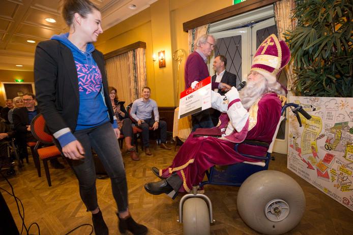 Marloes Fieret van Breda Barst neemt van Sinterklaas (Wilbert Willems) een cheque in ontvangst van 500 euro. Het festival kreeg ook de bokaal voor beste pitch op de Awarenessdag in Hotel Mastbos in Breda.