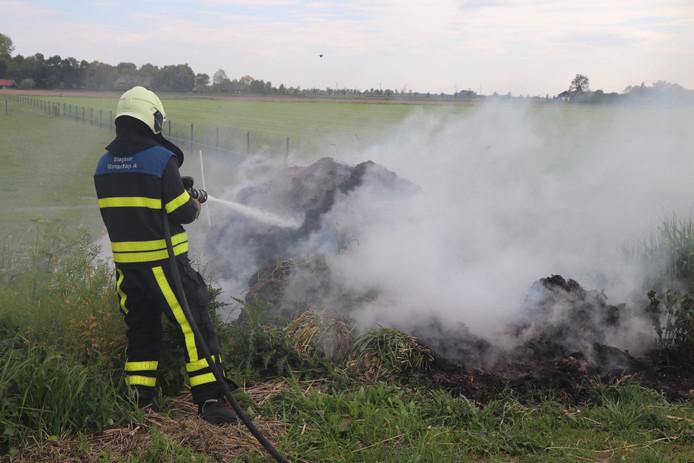 Brandweer blust brandende berg gras in Wijk en Aalburg