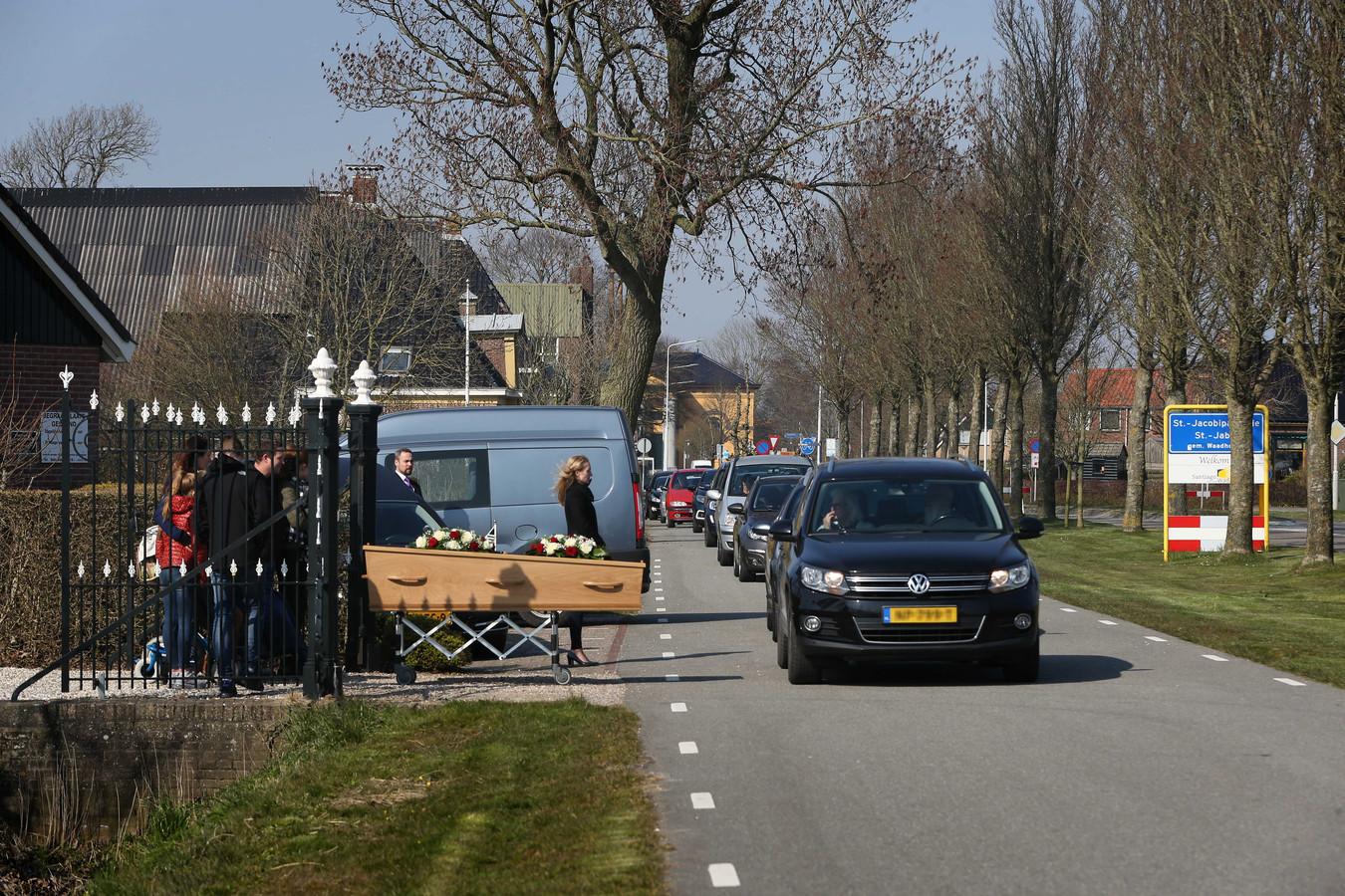 Nabestaanden nemen vanuit de auto afscheid van de overledene.