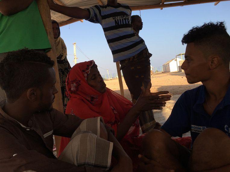 Mohammed Hussein (links) en Ayham Antar (rechts) luisteren naar een vrouw die in Jemen haar man heeft verloren bij een Saoedisch bombardement. Beeld Remco Andersen