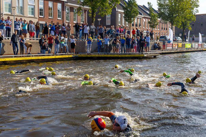 Aangemoedigd door de toeschouwers op de wal gaan de 24 zwemmers in het Steenwijkerdiep op weg voor hun 200 kilometer lange zwemtocht.