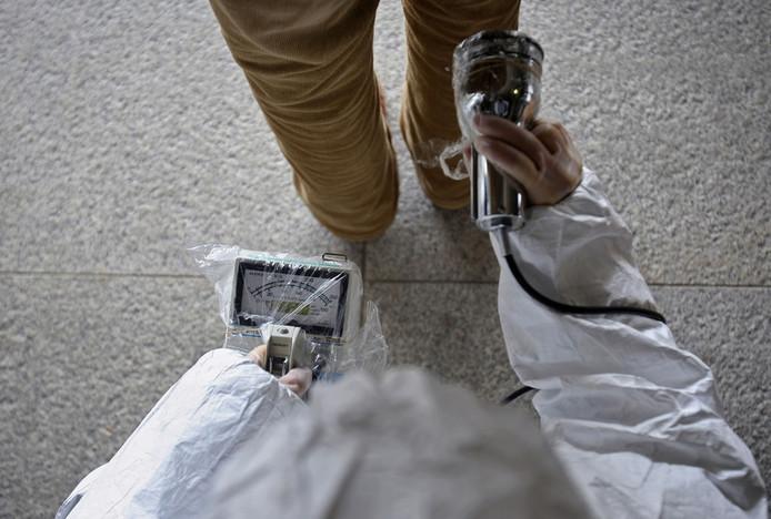 Een man wordt met meetapparatuur getest op radioactiviteit.