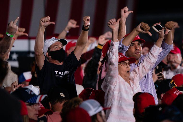 Aanhangers van Trump roepen en gebaren naar de pers tijdens een campagnebijeenkomst nadat de president zich negatief had uitgelaten over journalisten. Beeld Getty Images